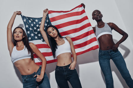Fourth of July. Three attractive young women holding American flag and looking at camera while standing against grey background