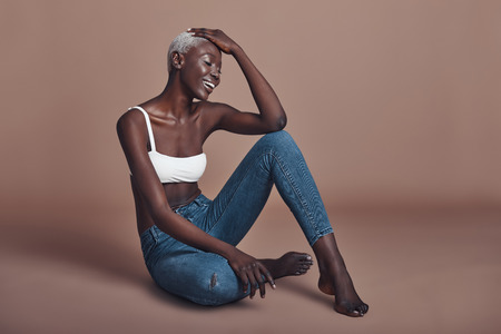 Unforgettable beauty. Attractive young African woman smiling while sitting against brown background Stok Fotoğraf