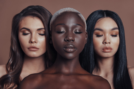 Perfect skin. Three attractive young women keeping eyes closed while standing against brown background