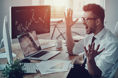 Great! Surprised young businessman in formalwear shouting and gesturing while using computer in the office