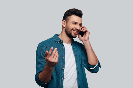 Good talk. Charming young man talking on smart phone and smiling while standing against grey background Stock Photo