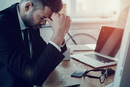 Stuck in office. Tired young man in formalwear massaging nose while sitting in the office Stock Photo
