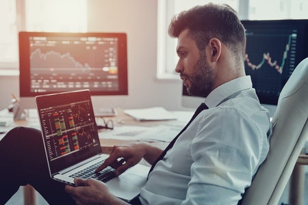 Beschäftigter Arbeitstag. Nachdenklicher junger Geschäftsmann in formeller Kleidung mit Laptop beim Sitzen im Büro Standard-Bild