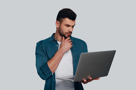 Considering next step. Thoughtful young man using laptop and keeping hand on chin while standing against grey background Stock fotó - 119185279