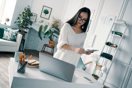 So busy. Beautiful young woman using digital tablet while working in home office