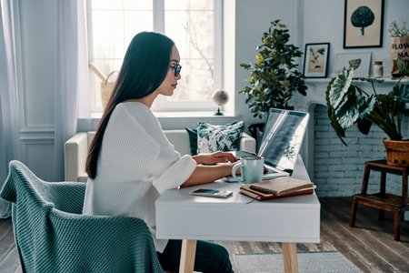 Taking care of business. Beautiful young woman working using laptop while sitting in home office