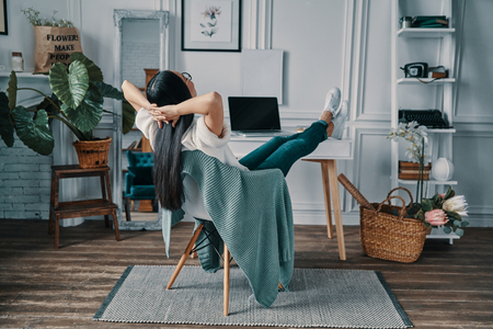 Total relaxation. Rear view of young woman keeping hands behind head while sitting in home office Stock Photo