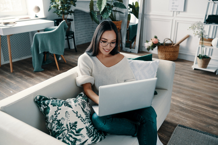 Surfing the net at home. Top view of young woman using laptop while spending time at home