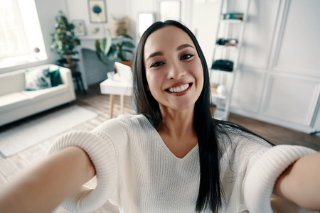 Perfect selfie. Attractive young woman looking at camera and smiling while taking selfie at home