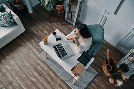 Hard decision to make. Top view of beautiful young woman working using computer while sitting in home office