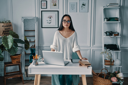 Beautiful and successful. Beautiful young woman looking at camera while standing in home office