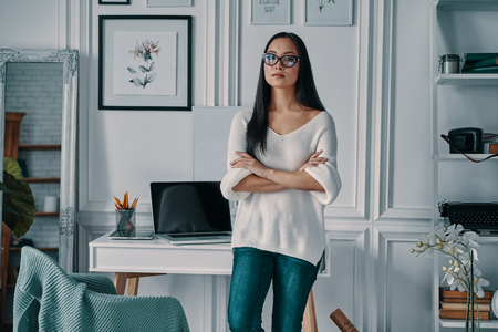 Young and full of ideas. Beautiful young woman looking at camera and keeping arms crossed while standing in home office