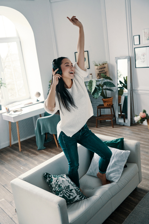 Superstar inside her. Full length of attractive young woman wearing headphones and smiling while dancing on sofa at home Stock Photo