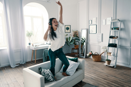 Going crazy. Full length of attractive young woman wearing headphones and smiling while dancing on sofa at home Stock Photo