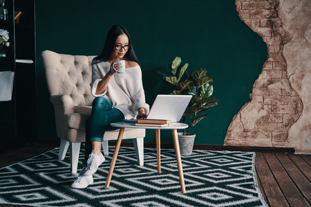 Exploring the net. Beautiful young woman using laptop and holding cup while sitting in the armchair
