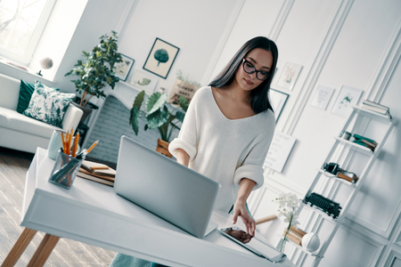 Getting things done. Beautiful young woman using laptop while working in home office