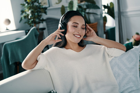 Favorite song. Attractive young woman wearing headphones and smiling while spending time at home
