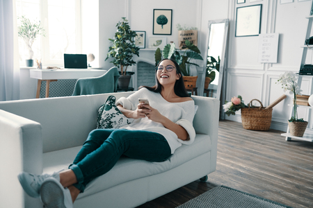 Something funny. Beautiful young woman holding smart phone and laughing while spending time at home
