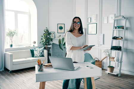 Successful entrepreneur. Beautiful young woman looking at camera and smiling while working in home office Stock Photo