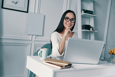 Confident young expert. Beautiful young woman smiling and looking at camera while sitting in home office
