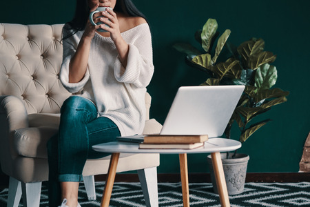Enjoying fresh coffee. Close up of young woman holding cup while sitting in the armchair