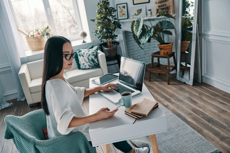 Working from home. Top view of beautiful young woman working using laptop while sitting in home office