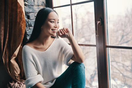 Good memories. Attractive young woman smiling and looking away while sitting on the window sill at home