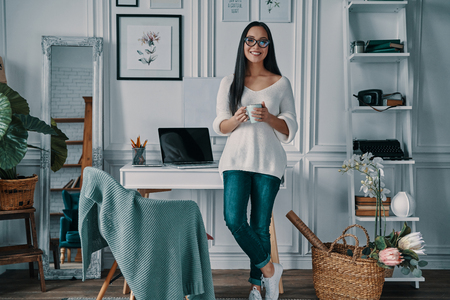 Coffee brings fresh ideas. Beautiful young woman looking at camera and smiling while standing in home office