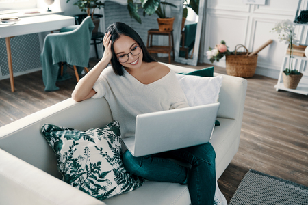 Time to relax. Top view of young woman using laptop while spending time at home