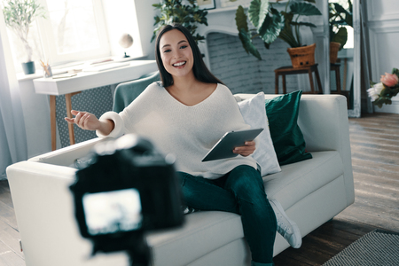 Beautiful influencer. Attractive young woman gesturing and smiling while making new video for her blog