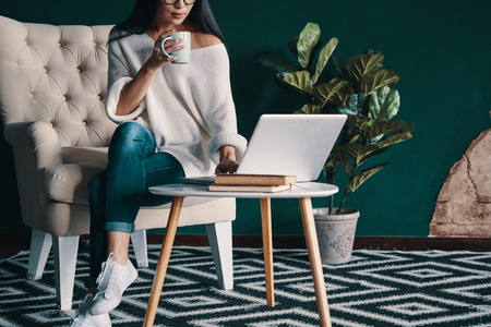 Coffee keeps her up. Close up of young woman using laptop and holding cup while sitting in the armchair