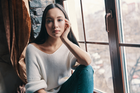 No worries. Attractive young woman looking at camera while sitting on the window sill at home 免版税图像