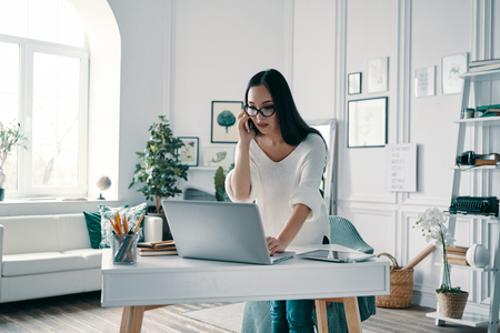 Always available. Beautiful young woman using computer and talking on the phone while working in home office Stock Photo