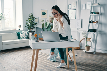 Young expert. Beautiful young woman using computer and talking on the phone while working in home office