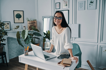 Happy businesswoman. Beautiful young woman looking at camera and smiling while standing in home office