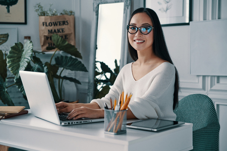 Young and smart. Beautiful young woman smiling and looking at camera while sitting in home office Stock Photo