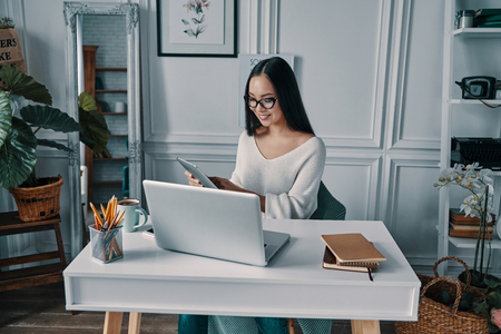 Great idea! Beautiful young woman smiling and working using digital tablet while sitting in home office