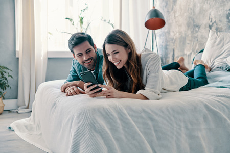 Everything is online. Beautiful young couple using smart phone and smiling while spending time in bed at home