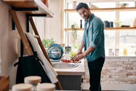 Want some salad? Handsome young man in casual wear chopping food and smiling while standing in the kitchen at home