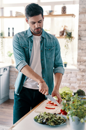 Making salad. Handsome young man in casual wear cutting vegetables while standing in the kitchen at home 스톡 콘텐츠