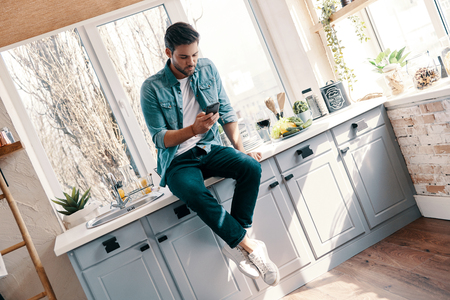 Texting to friends. Handsome young man in casual wear using his smart phone while sitting in the kitchen at home 免版税图像