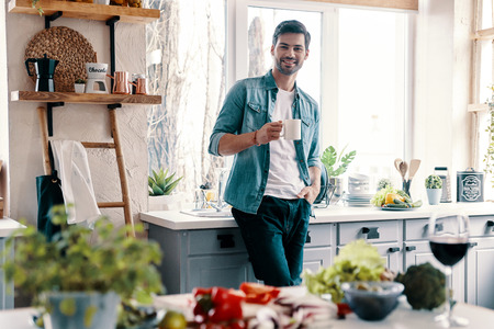 Modern man. Handsome young man in casual wear looking at camera and having a hot drink while standing in the kitchen at home 스톡 콘텐츠