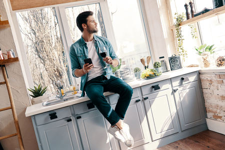 Thinking about something. Handsome young man in casual wear drinking wine and using his smart phone while sitting in the kitchen at home