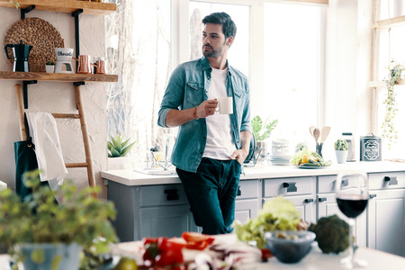 Taking time to think. Handsome young man in casual wear looking away and having a hot drink while standing in the kitchen at home 스톡 콘텐츠
