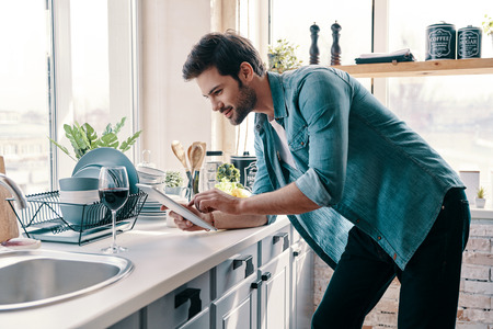 What to cook? Handsome young man in casual wear using digital tablet and smiling while standing in the kitchen at home