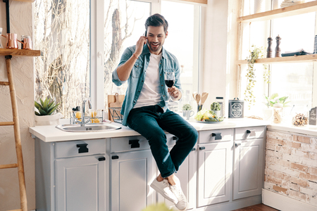 Inviting friends for dinner. Handsome young man in casual wear drinking wine and talking on the phone while sitting in the kitchen at home 스톡 콘텐츠