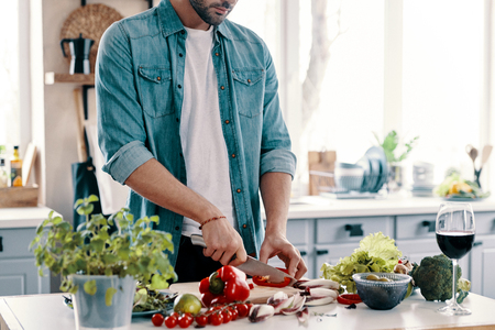 Healthy eating. Close up of young man in casual wear cutting vegetables while standing in the kitchen at home