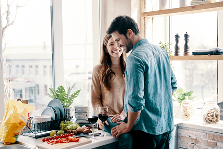 He will never let her go. Beautiful young couple cooking dinner and drinking wine while standing in the kitchen at home Stock Photo