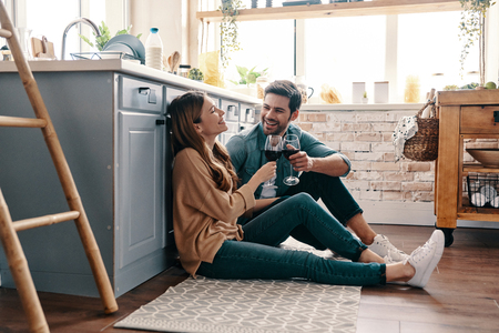Love is in the air. Beautiful young couple drinking wine while sitting on the kitchen floor at home