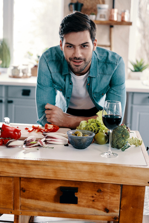 Cooking healthy dinner. Handsome young man in casual wear looking at camera and smiling while standing in the kitchen at home